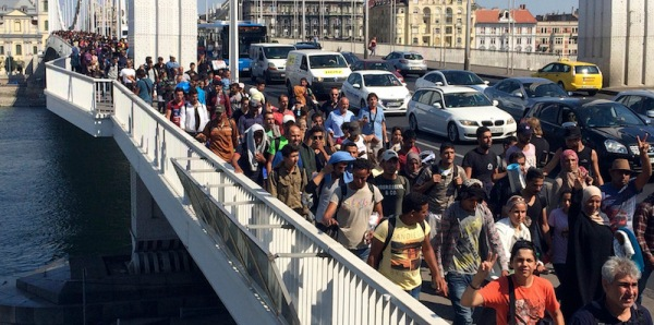 Hundreds of migrants cross the river Danube in Budapest, Friday Sept, 4, 2015, after they decided to walk toward Austria. Thousands have been camped out at Budapest's Keleti train station for days, before they decided to try and reach their destination on foot. (AP Photo/Bela Szandelszky)